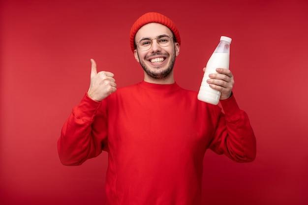 Foto van gelukkig man met baard in rode kleding houdt melk zuivel voedsel geeft duim omhoog, geïsoleerd op rode achtergrond.