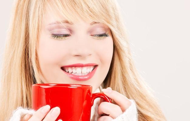 Foto van gelukkig meisje met rode mok