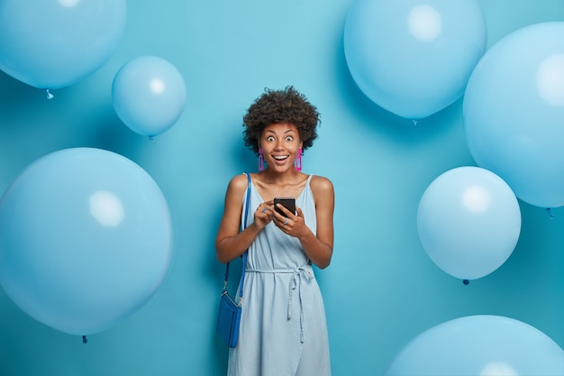 Foto van gelukkig onder de indruk vrouw die op corporatieve partij is, gekleed in alles blauw, smartphone vasthoudt, verrast om onverwacht bericht van formele echtgenoot te krijgen, poseert in de buurt van decoraties met ballonnen