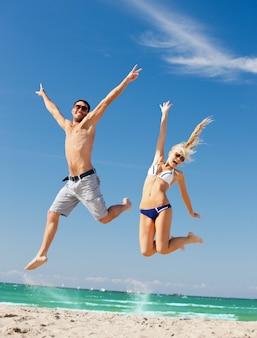 Foto van gelukkig paar dat op het strand springt (focus op vrouw)
