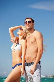 Foto van gelukkig paar in zonnebril op het strand (focus op man)