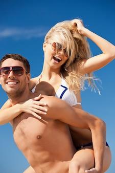 Foto van gelukkig paar in zonnebril op het strand (focus op vrouw)