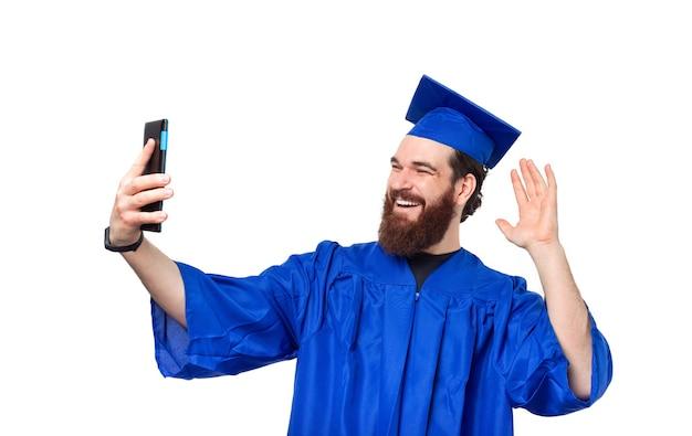 Foto van gelukkig student man blauw gewaad dragen en selfie maken met smartphone