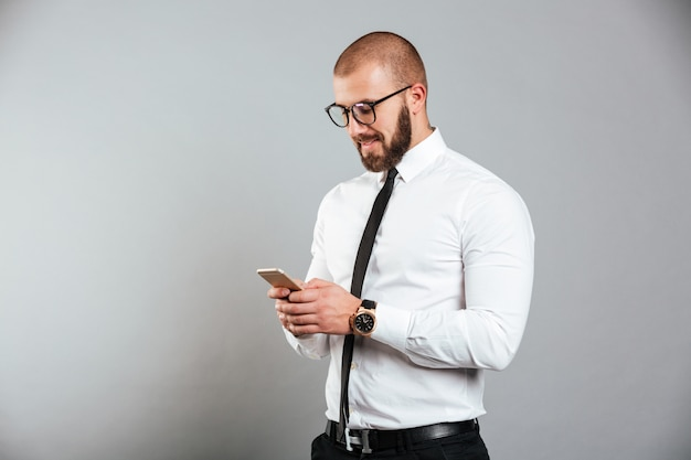 Foto van gelukkig succesvolle man in glazen en stropdas communiceren terwijl smartphone in handen, geïsoleerd over grijze muur