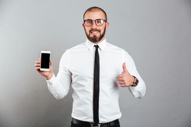 Foto van gelukkig succesvolle man in glazen en stropdas demonstrerende mobiele telefoon en duim opdagen, geïsoleerd over grijze muur