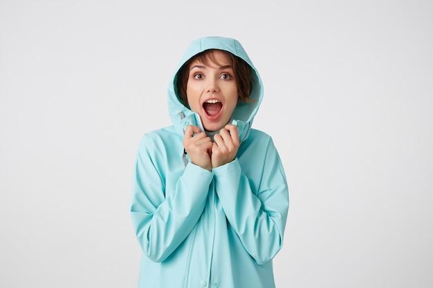 Foto van gelukkig verbaasd jonge mooie vrouw in blauwe regenjas, met een kap op zijn hoofd, kijkt naar de camera met verrassende uitdrukkingen, staat over witte muur.