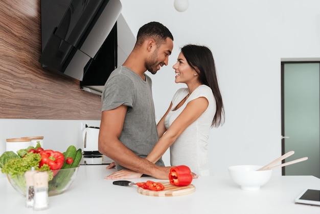 Foto van gelukkig verliefde paar in de keuken knuffelen tijdens het koken.