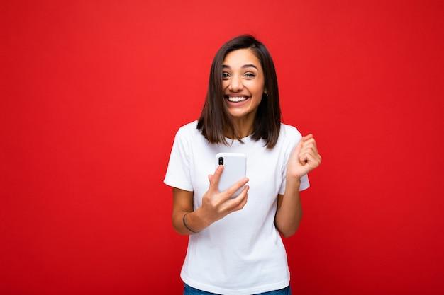 Foto van gelukkige aantrekkelijke gekke verbaasde verrast jonge vrouw, gekleed in casual stijlvolle kleding permanent geïsoleerd op achtergrond met kopie ruimte houden en met behulp van mobiele telefoon camera kijken.