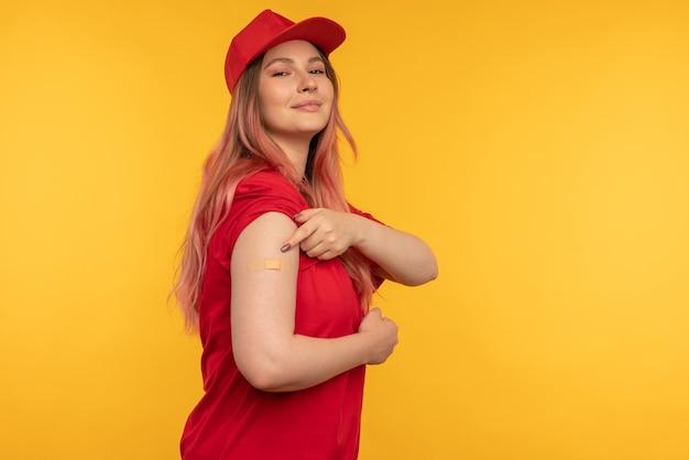 Foto van gelukkige aardige jonge vrouw goed humeur punt vinger vaccinatie geïsoleerd op gele kleur achtergrond