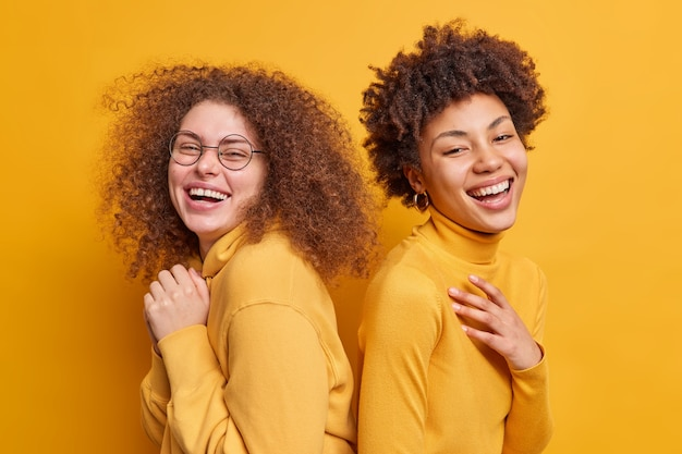 Foto van gelukkige diverse vrouwen die achter elkaar staan glimlachen in grote lijnen positieve emoties uiten die geamuseerd worden door iemand die over een gele muur geïsoleerd is. diversiteitsras en vriendschapsconcept.