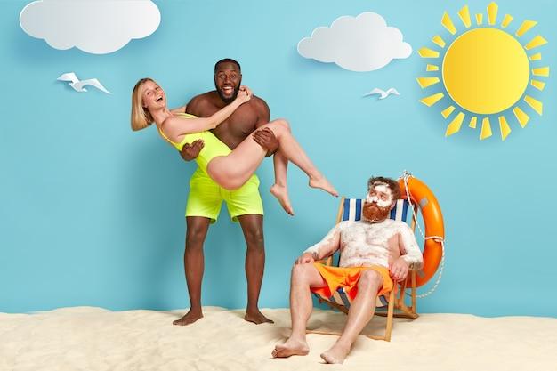 Foto van gelukkige donkere man draagt vriendin in zwembroek op handen