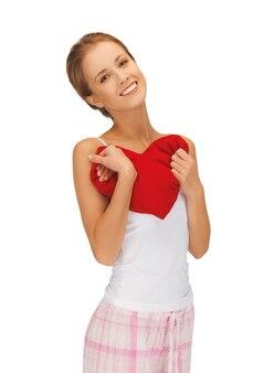 Foto van gelukkige en lachende vrouw met hartvormig kussen