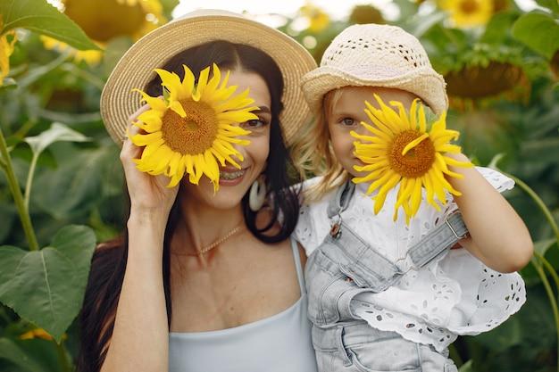 Foto van gelukkige familie. moeder en dochter. familie samen op zonnebloemgebied.