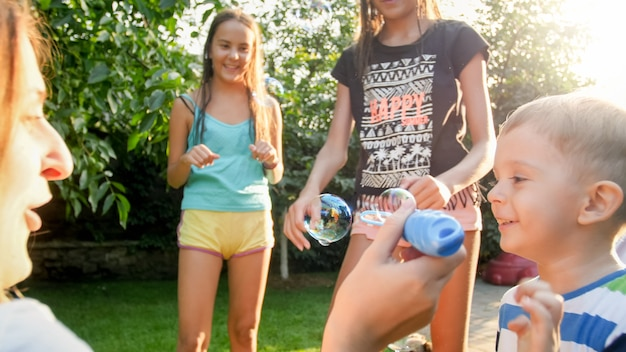 Foto van gelukkige familie spelen met zeepbellen in de achtertuin van het huis. familie spelen en plezier hebben buiten in de zomer