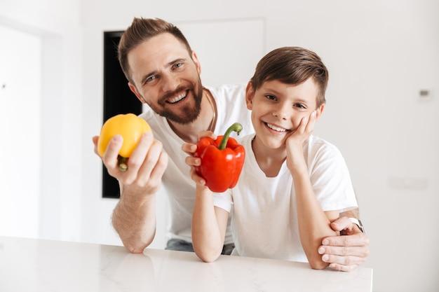 Foto van gelukkige gezonde vader en zoon die thuis samen glimlachen, terwijl ze verse zoete papieren vasthouden