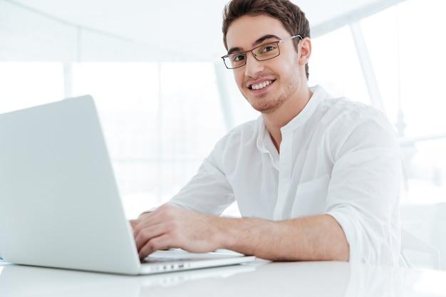 Foto van gelukkige jonge man gekleed in wit overhemd met behulp van laptopcomputer. kijk naar de camera.