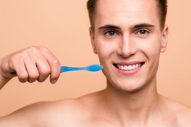 Foto van gelukkige jonge man met tandenborstel geïsoleerd beige
