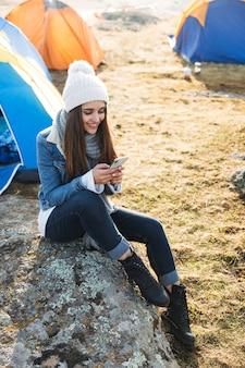 Foto van gelukkige jonge vrouw buiten met tent in gratis alternatieve vakantiecamping over bergen met behulp van mobiele telefoon.
