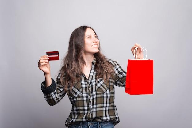 Foto van gelukkige jonge vrouw met creditcard en rode boodschappentas en wegkijken