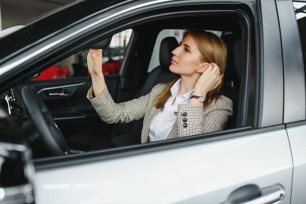 Foto van gelukkige jonge vrouw zit in haar nieuwe auto. concept voor autoverhuur