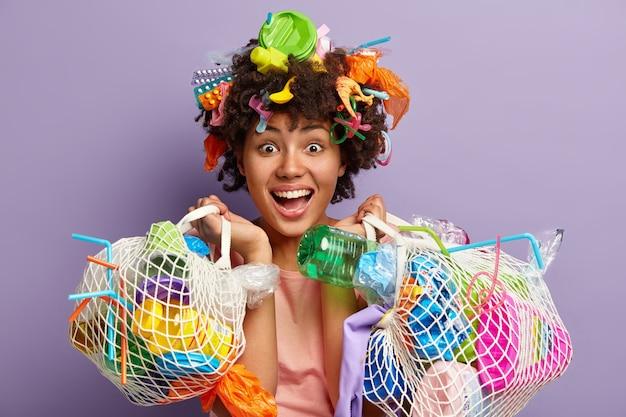 Foto van gelukkige jonge vrouwelijke vrijwilliger draagt tassen met afval, kijkt vreugdevol, blij om goede dingen te doen voor het milieu en de planeet waar ze woont, geïsoleerd over paarse muur.