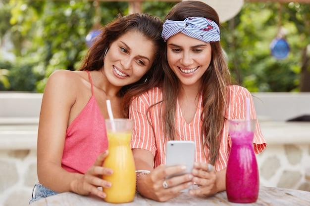 Foto van gelukkige jonge vrouwen hebben dezelfde relaties, surfen op internet op hun mobiele telefoon, lees de opmerkingen onder de post, drinken verse cocktails in de cafetaria