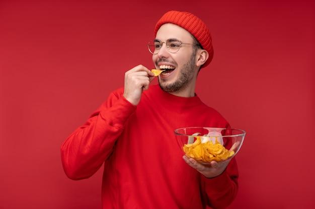 Foto van gelukkige man met baard in glazen en rode kleding. houdt en eet een bord chips, geïsoleerd op rode achtergrond.