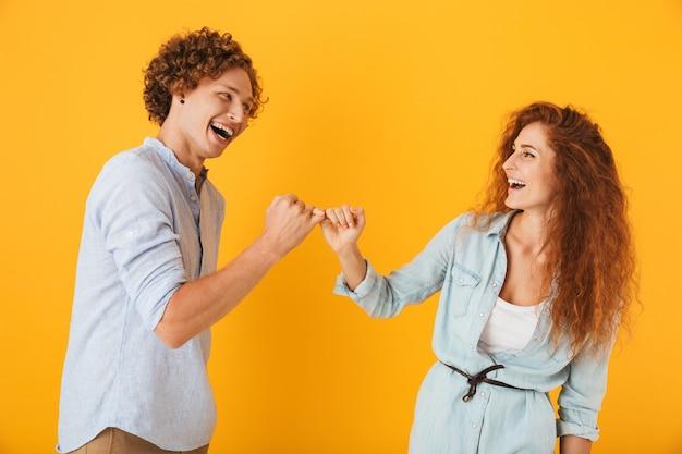 Foto van gelukkige mensenman en vrouw die glimlachen en elkaars kleine vingers in verzoening of vriendschap haken, die over gele achtergrond wordt geïsoleerd