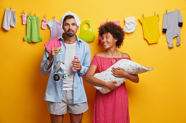 Foto van gelukkige moeder houdt pasgeboren baby en kijkt naar man die helpt met de verpleging van het kind, mobiele, zuigfles houdt. jonge ouders zorgen voor een kleine baby. familie, ouderschap concept.