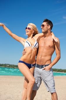 Foto van gelukkige paar in zonnebril op het strand.