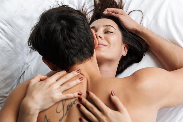 Foto van gelukkige paar knuffelen en kussen samen, liggend in witte bed thuis