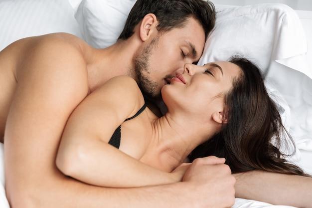 Foto van gelukkige paarman en vrouw die samen kussen, terwijl liggend in bed thuis of hotelappartement