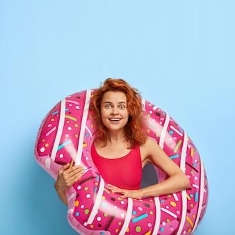 Foto van gelukkige roodharige vrouw gekleed in bikini