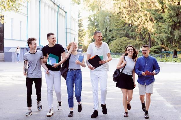 Foto van gelukkige universitaire studenten die na klassen naar huis gaan