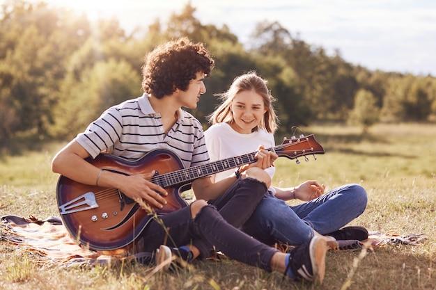 Foto van gelukkige vrienden die zichzelf betreden, liedjes zingen en gitaar spelen, vrolijke uitdrukkingen hebben, op de grond zitten, gekleed in vrijetijdskleding, genieten van een zonnige zomerdag op de natuur. levensstijl concept