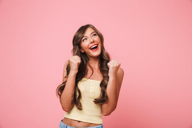 Foto van gelukkige vrouw 20s met lang bruin haar vreugde en genieten van zijn doelstellingen met gebalde vuisten als succesvol persoon, geïsoleerd op roze achtergrond