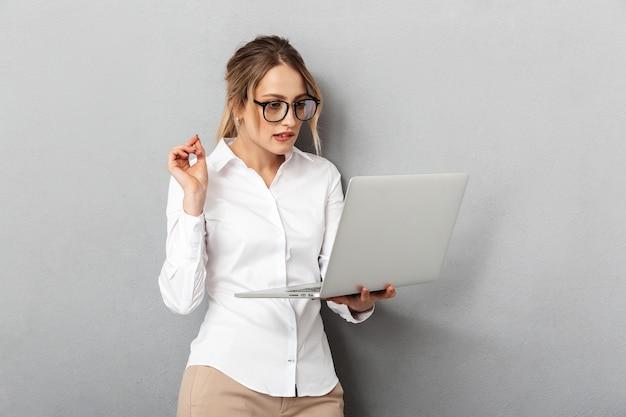 Foto van gelukkige vrouw die een bril draagt en laptop op kantoor houdt, geïsoleerd