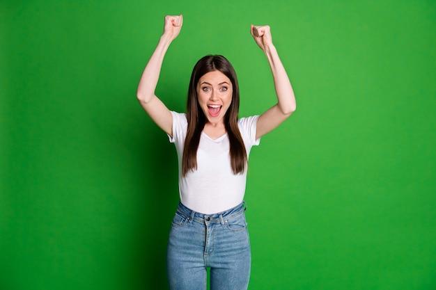 Foto van gelukkige vrouw draagt casual witte t-shirt jeans armen omhoog open mond geïsoleerde groene kleur achtergrond