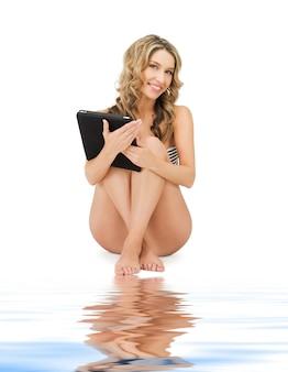 Foto van gelukkige vrouw in bikini met tablet pc computer