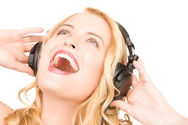 Foto van gelukkige vrouw in koptelefoon over wit