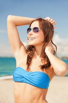 Foto van gelukkige vrouw in zonnebril op het strand.