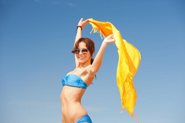 Foto van gelukkige vrouw met gele sarong op het strand.