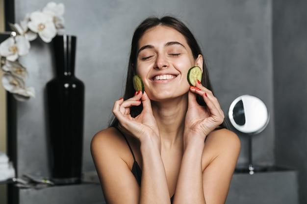 Foto van gelukkige vrouw met lang donker haar en een gezonde huid die komkommer op het gezicht zet