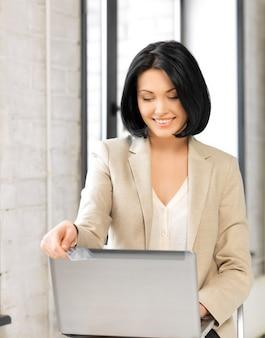 Foto van gelukkige vrouw met laptopcomputer en creditcard.
