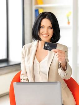 Foto van gelukkige vrouw met laptopcomputer en creditcard