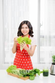 Foto van gelukkige vrouw met sla in de keuken