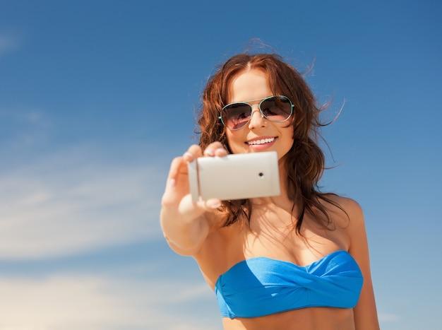 Foto van gelukkige vrouw met telefoon op het strand.