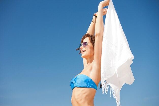 Foto van gelukkige vrouw met witte sarong op het strand.