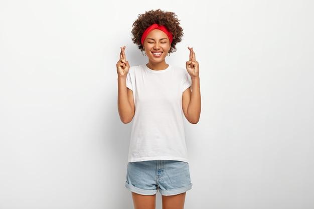 Foto van gelukkige vrouwelijke student kruist vingers, gelooft in geluk op examen
