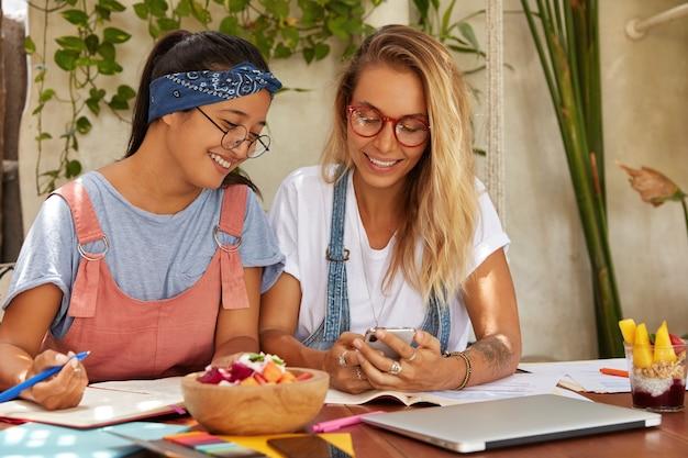 Foto van gelukkige vrouwen van verschillende rassen lachen als bekijk grappige video op internetwebsite